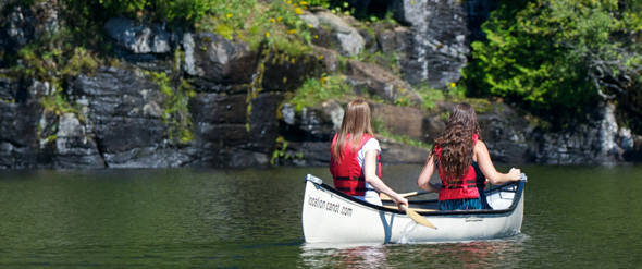 Two canoers paddling toward a rock bluff.