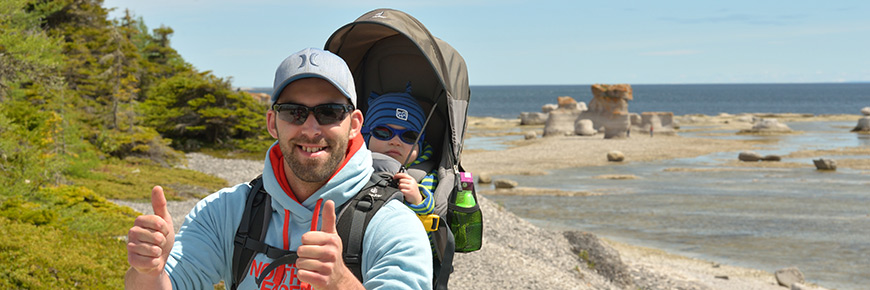 Photograph of a father with his child in a baby backpack with monoliths and the sea in the background