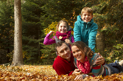 A small family plays in leaves during the fall.