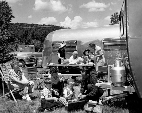 A family enjoying a beautiful summer day at a trailer campground