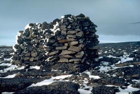 Stones are piled high on  the rocky landscape to form a cairn.