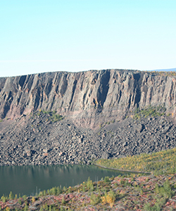 Rocky cliff with trees at the edge of a lake, with Great Slave Lake behind