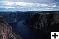Aerial view of the majestic Western Brook Pond fiord with its steep cliffs and the river flowing at the bottom.