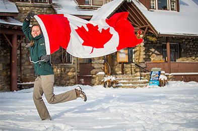 Woman running in the snow in front of Jasper Information Center while bearing the Canadian flag