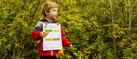 Boy holding a clipboard, an activity sheet and a pencil.