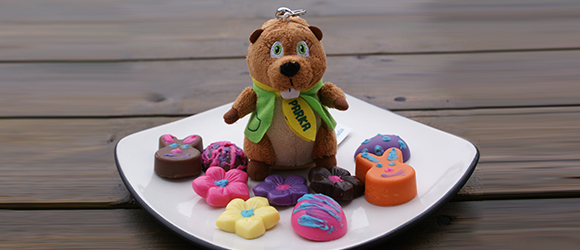 A Parka stuffed toy on a plate, surrounded by decorated chocolates