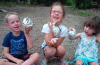 Kids are having fun making campfire muffins in oranges.