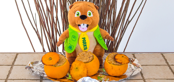 Parka plushy is standing in front of 3 muffins baked in oranges.