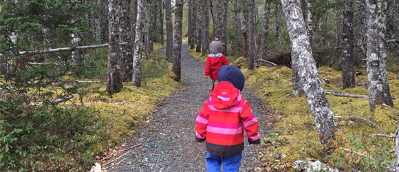 Two kids walking on a trail in the forest