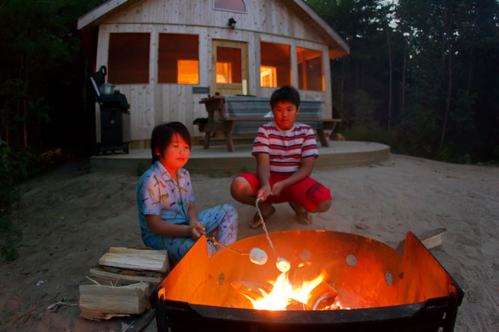 Two children have fun roasting marshmallows over a campfire on Beausoleil Island.