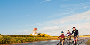 Family enjoying a bicycle ride with a lighthouse in the background.
