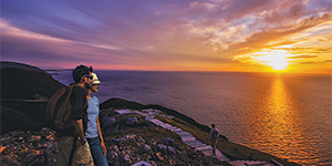 Young couple admiring the sunset on Cabot Trail.