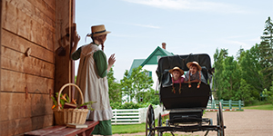 A Parks Canada interpreter dressed as Anne of Green Gables greets two young visitors.