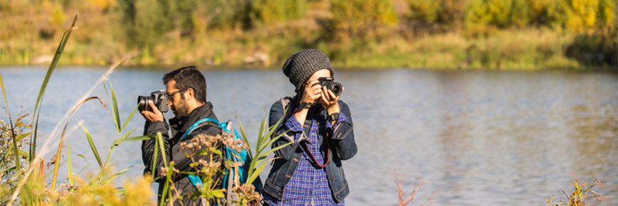 Two photographers take wildlife photos by a lake.