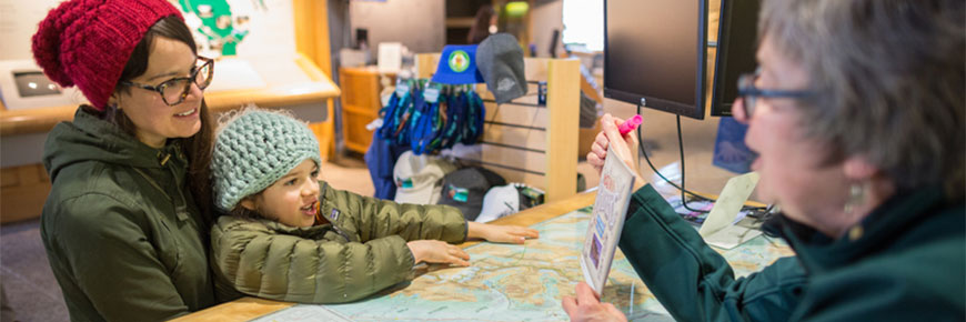 A mother and daughter look at a map with a Parks Canada employee.