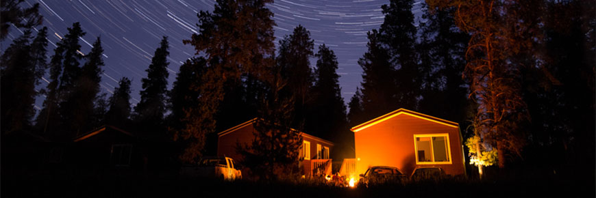 Two cabins lie underneath a starry night sky.