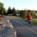 A biker rushing along the bike path that follows the Lairet River in Cartier-Brébeuf National Historic Site, with a view of the river and the city in the background.