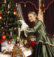 A woman in period costume hangs decorations on a Christmas tree.