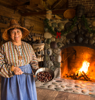 A woman holding chestnuts stands in front of a fireplace.