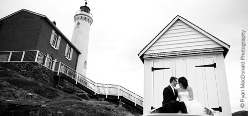 A bride and groom sitting in from of Fisgard Lighthouse.