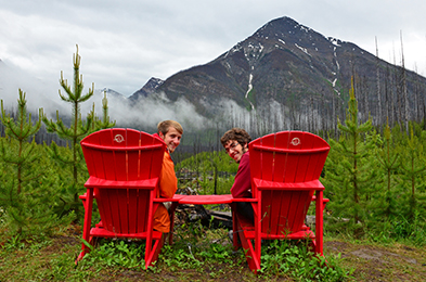 Two men enjoy red chairs at a scenic vista