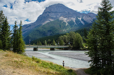A small boy by the Kicking Horse River at Field, British Columbia in Yoho National Park