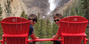 Two men take a break at the red chairs at Takakkaw Falls