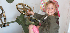 A six years old in WW2 kids dress-up uniform maneuvers the 12-poundersquick-firing guns controlling wheels