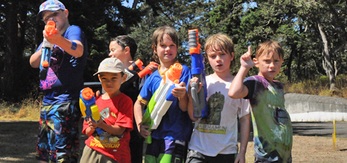 Six young boys, water guns in hand and already wait are posing