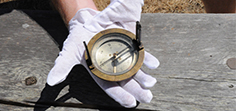 Hands with white gloves on holding an WWI military compass