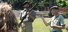 Parks Canada staff in uniform hold a historic riffle and ammunitions