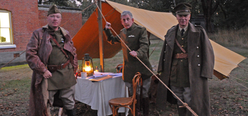 Three re-enactors in period uniform from WW2 pose in front of a tent and a desk lid by a lantern