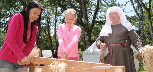 Two teenage girls learn to beat flax in the medieval customs