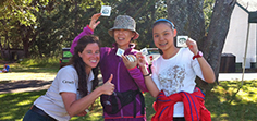 An Asian mom and her daughter waving their Species at Risk stickers and temporary tattoos after a fun activity with a Parks Canada interpreter