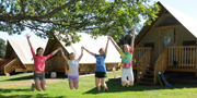 Four pre-teen young girls jumping together with arms up, in front of three oTENTik tents