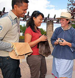 Parks Canada costumed interpreter shows couple artifacts