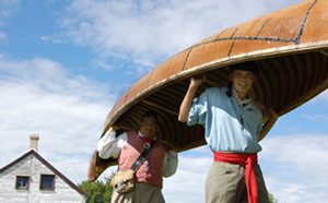 Costumed guides carry a canoe