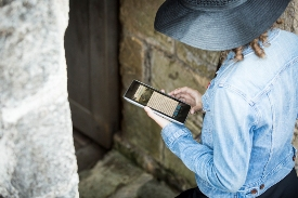 Visitor uses Explora GPS handheld device in salllyport, Fort Anne National Historic Site