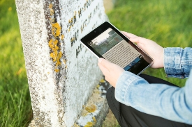 Visitor uses Explora GPS handheld device in the cemetery, Fort Anne National Historic Site