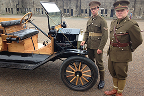 image: WWI-era car, soldier and officer