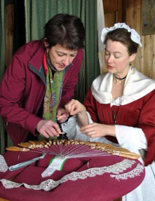 An interpreter shows a visitor how to make lace