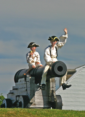 Two young visitors sitting on cannon