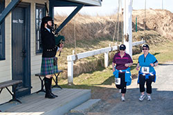 Two women running with bagpiping playing at Halifax Citadel National Historic Site