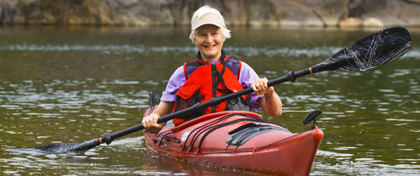 A white-haired lady in a kayak on a calm lake.