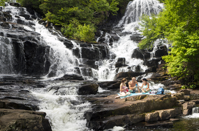 A young family picnicking by the Waber falls.