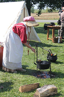 Wife of militiaman from the war of 1812 serving the traditional meal of soldiers: the meatsoup