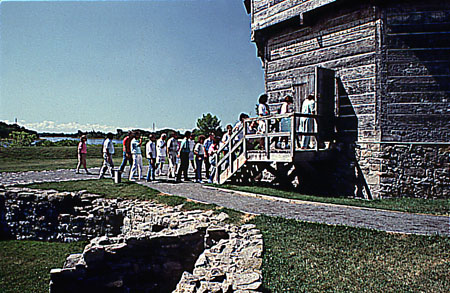 A group of visitors are waiting to enter the octagonal blockhouse of Coteau-du-Lac