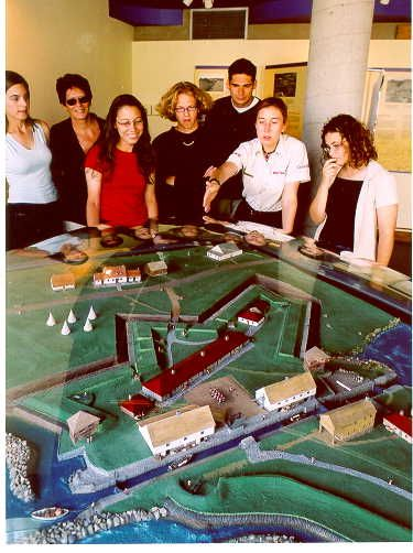 A group of visitors in front of the site's model representing the British military occupation around 1820