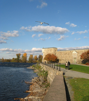People are eating in the park. In the background, there are the fort and the Richelieu River