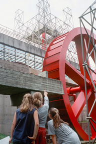 Three girls look at the big red wheel of the blast furnace.